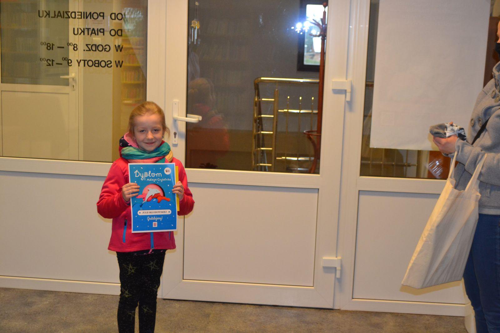Dziewczynka na tle bibliotecznych drzwi trzymająca w dłoniach dyplom.