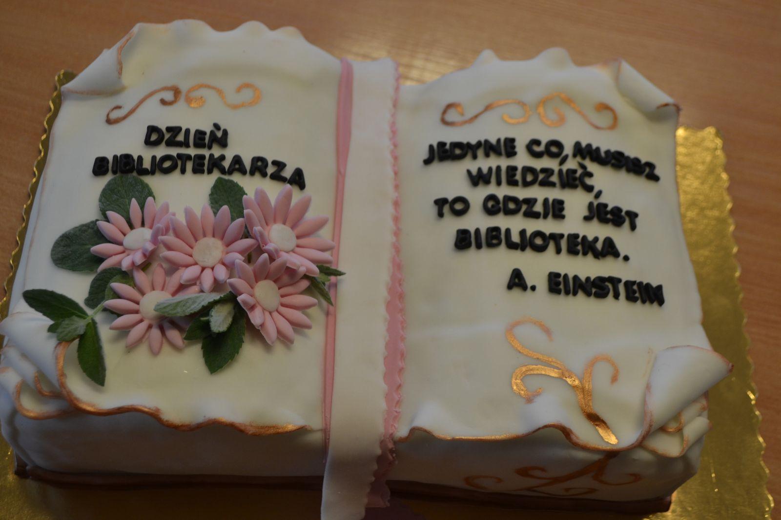 Zdjęcie tortu w kształcie otwartej księgi; na lewej stronie różowe kwiatki i napis Dzień Bibliotekarza, na prawej stronie cytat: Jedyne, co musisz wiedzieć, to gdzie jest biblioteka. A. Einstein.