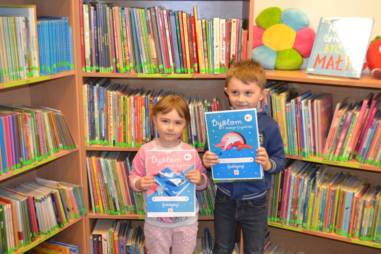 Dziewczynka i chłopczyk na tle regałów z książkami dla dzieci trzymający przed sobą w dłoniach dyplomy.