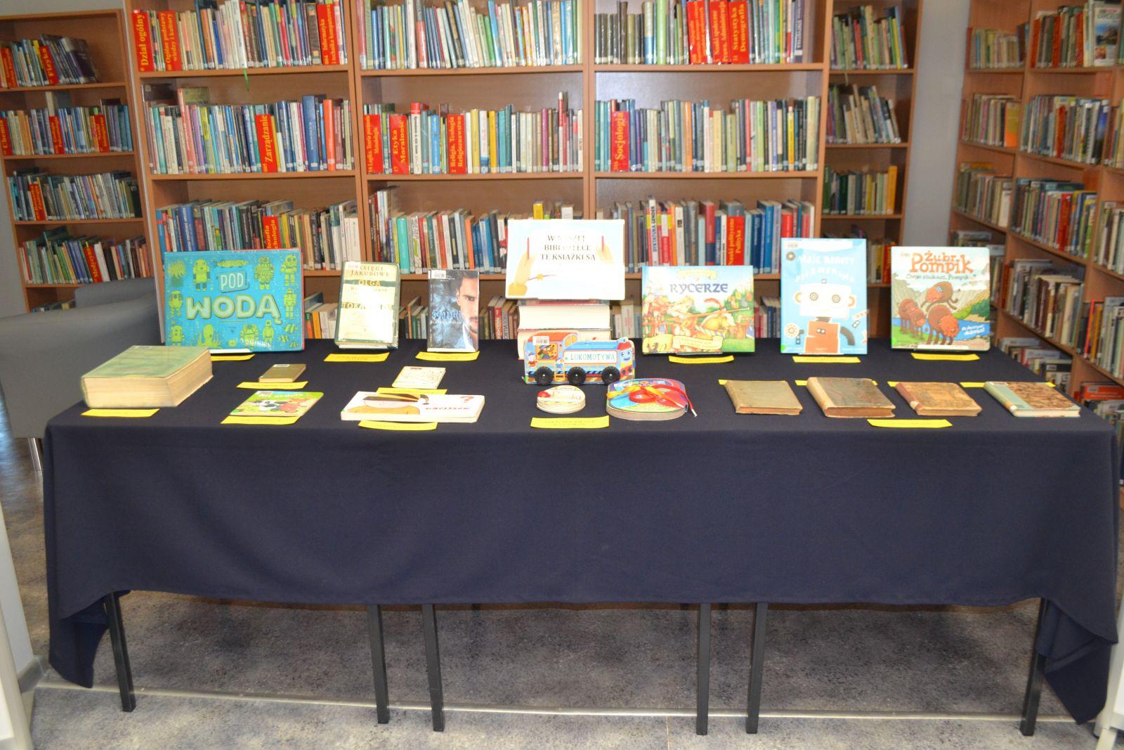 Wystawka książek na tle bibliotecznych regałów.