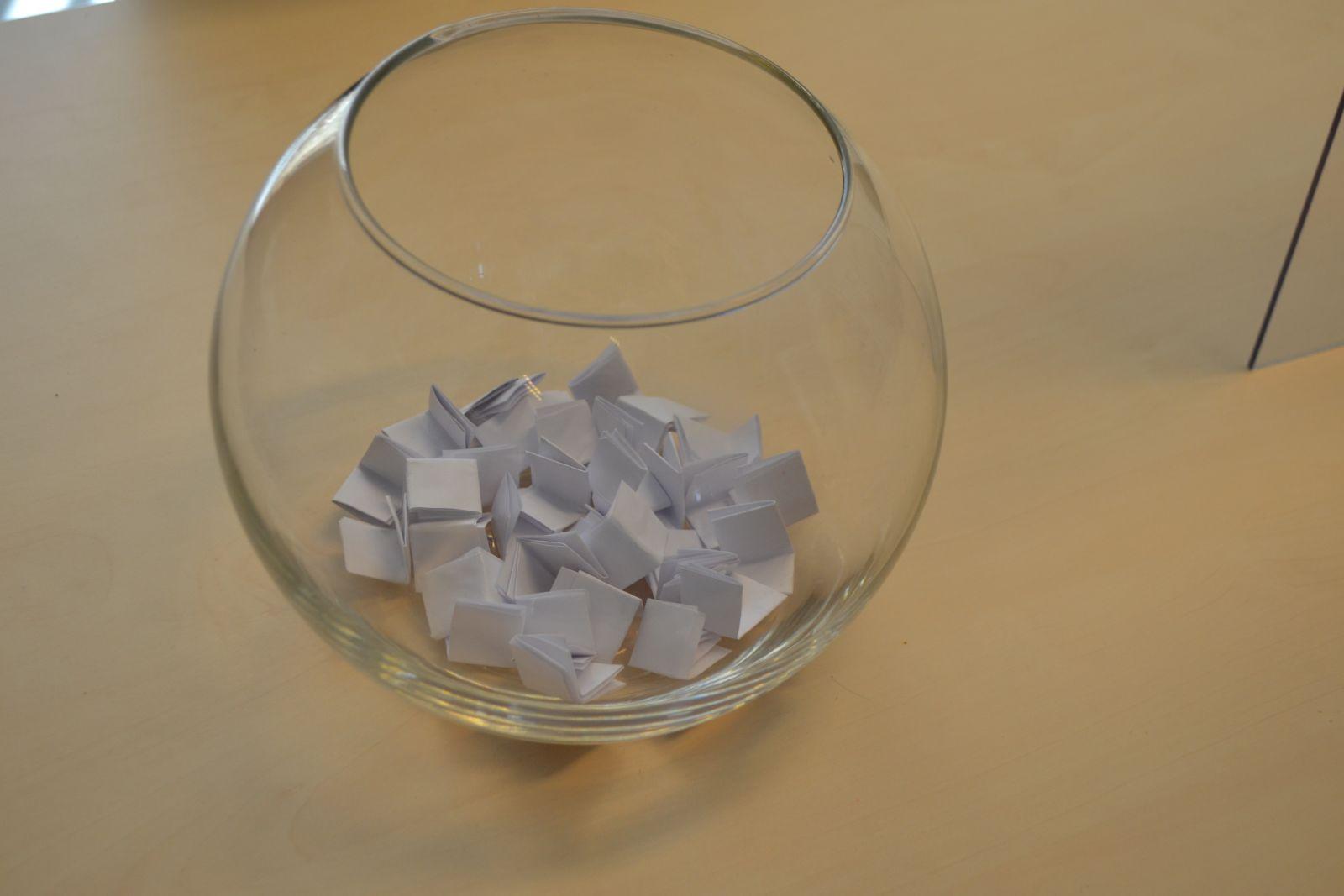 Zdjęcie szklanego naczynia w kształcie kuli z losami w środku.